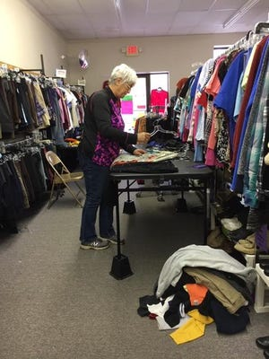 Volunteer Marcia Ricker sorts clothing for the June's Place Thrift Store in Reading.