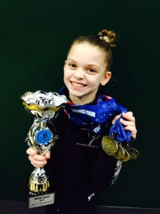 Annie Beard, 10, shows off the numerous awards she has won competing in gymnastics.