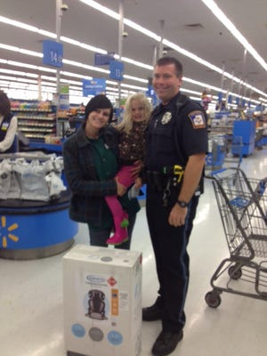 Officer Ben Hall, Lexi DeLorenzo and her daughter with the car seat at Walmart on Friday evening.