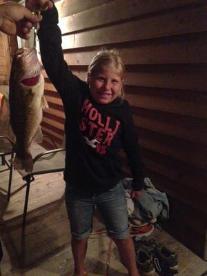 Kara Lambrecht, 8, shows the 15-inch largemouth bass she caught on a lake near Crandon.