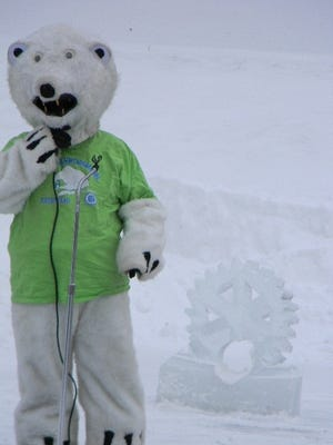 Bob Venne wore his polar bear costume for the annual Polar Bear Plunge. An ice sculpture of the Rotary wheel is beside him.
