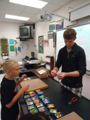 Josh Fritsche helps a student put beads and spinners on to a lure.