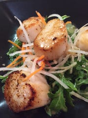 Mark Eastman, chef/owner of Chefs' Haven in Hockessin, recently made seared scallops with yuzu wasabi vinaigrette during an Asian seafood cooking class at his Old Lancaster Pike shop.