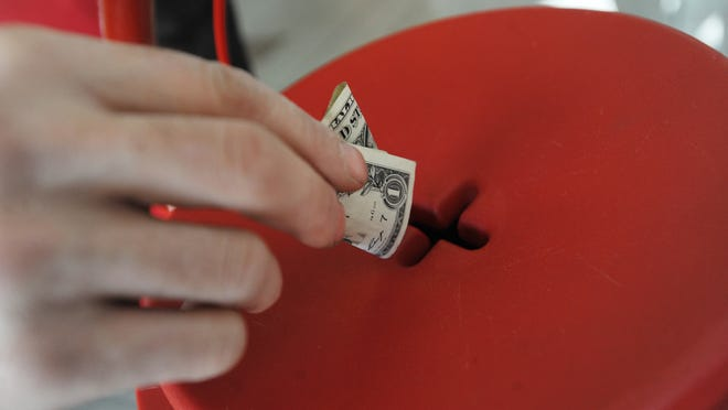 Holiday shoppers donate to the Salvation Army Red Kettle in this December 2011 file photo.