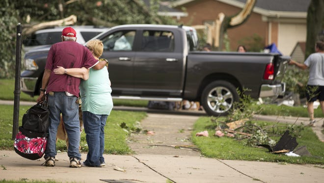 A couple hug  amid damage after a tornado that touched down in Kokomo on Wednesday, Aug. 24, 2016.