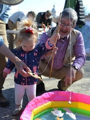 Annie Balderson, 22-months, caught a magnet fish while her grandfather, Carl Balderson watches her at Earth Day Staunton on Saturday. The little girl, who lives in Louisville, Kentucky, was visiting her grandparents this weekend.