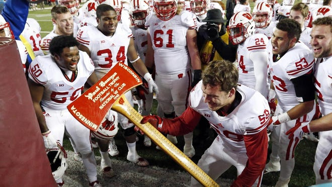 "Wisconsin linebacker Joe Schobert ""chops"" the goal post with the prized Paul Bunyan axe after Wisconsin beat Minnesota 31-21 Saturday, Nov. 28, 2015, in Minneapolis."