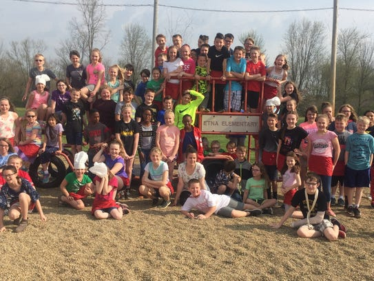 Students gather on existing playground equipment, which