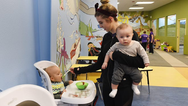 Taryn McQueen feeds Preston Banke while holding Lincoln Murff at The Treehouse at Raintree Athletic Club. More than 400 children are on a waiting list for county assistance for child care.