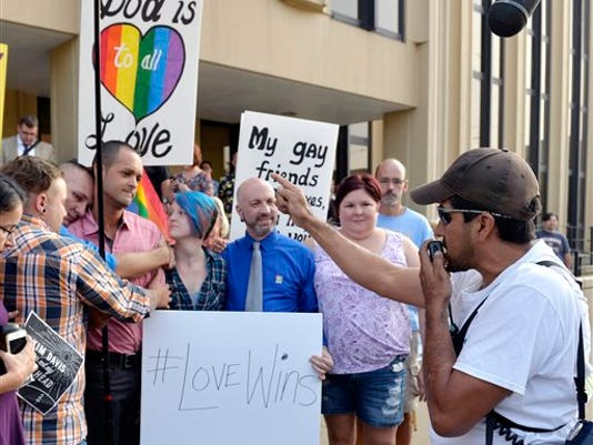 Edgar Orea, right, preaches to a group of same sex marriage supporters that have gathered outside the Carl D. Perkins Federal Building in Ashland, Ky., Thursday, Sept. 3, 2015. Hundreds gathered awaiting the arrival of Rowan County Clerk Kim Davis who has been ordered to appear in federal court to explain why she is refusing to issue marriage licenses despite a federal order to do so.