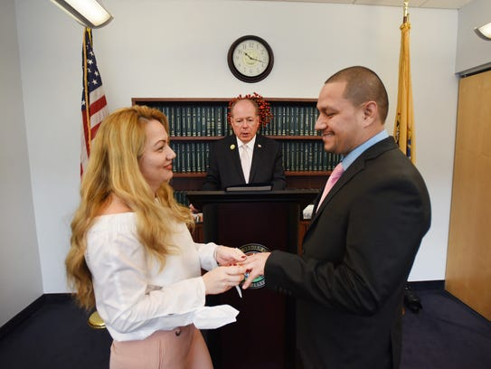 Bergen County Clerk John Hogan performs the wedding ceremony as the couple, Victor Sosa and Brenda Aguilar exchange wedding rings at his office at the Bergen County Administrative Buildings in Hackensack on 02/14/18.