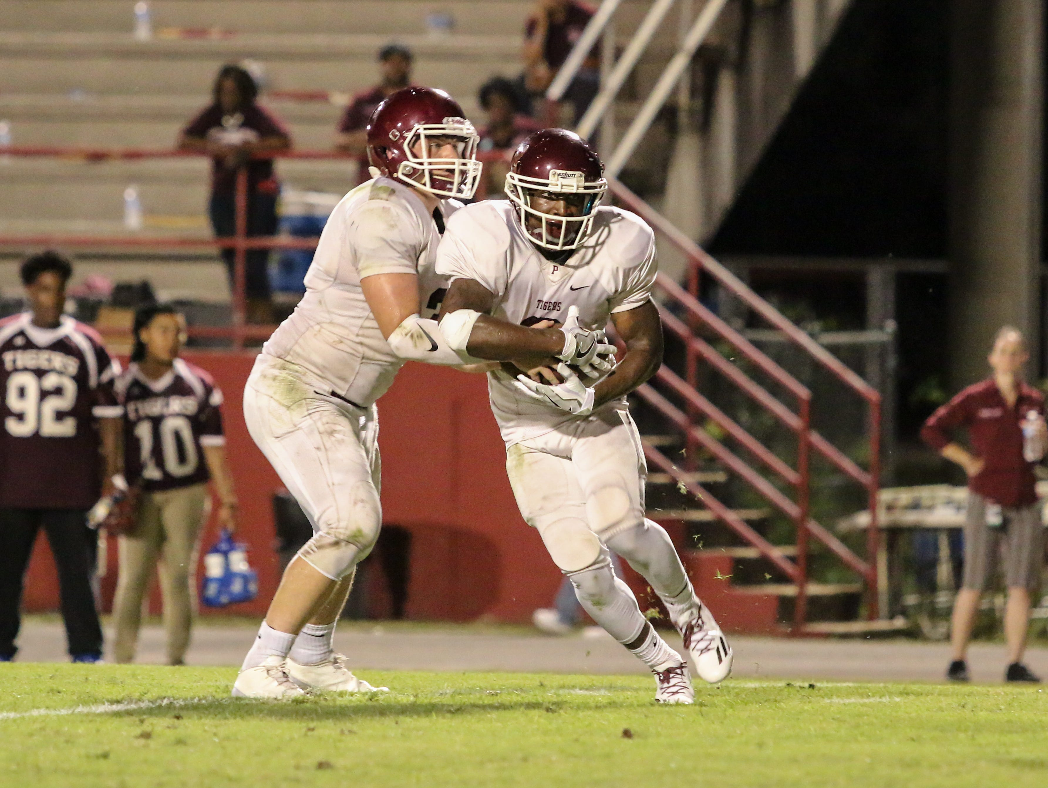 Pensacola's Tyrese Albritton (2) takes the handoff from quarterback Ashton Stephens (3) Friday night at Pine Forest High School.
