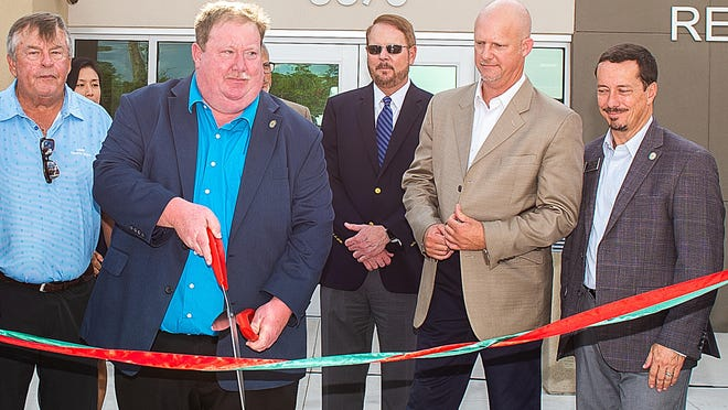 St. Johns County Commissioner Paul Waldron cuts a ribbon during an opening ceremony for a new fire station. He is in critical care because of the coronavirus.