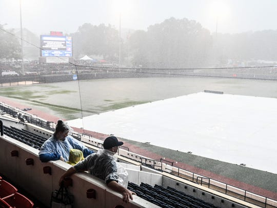 Fans watched the rain fall during a weather delay before