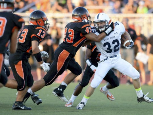 Central York's Micah Richardson pulls down West York's Noah Bowers, right, during the Bulldogs' 41-20 victory Friday night at Central York High School. (Kate Penn -- GameTimePA.com)