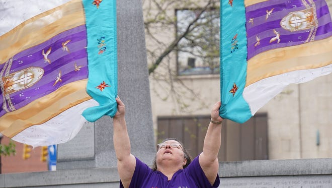 Janet Salim rhythmically waves flags during a song at the National Day of Prayer ceremony in the square on Thursday.