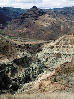 The Blue Basin Overlook Trail in John Day Fossil Beds National Monument features gorgeous views of volcanic ash that has turned to blue-green claystone, now exposed to the weather and carved into towering cliffs. The three-mile trail loops around the rock formation and up the hillsides of the surrounding John Day River Valley.