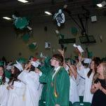 Northridge High School graduates throw their caps Sunday during the commencement ceremony.