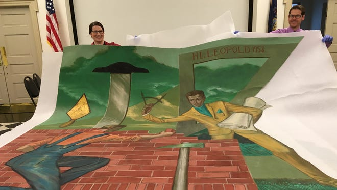 Rachel Warner, collections manager of the York County History Center, and Dan Roe, vice president of interpretation, hold up a section of the 1959 Drovers and Mechanics Bank mural.