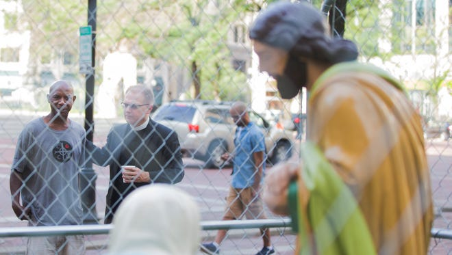 """Ralph Howard and The Rev., Senior Pastor Stephen Carlsen discuss the statue of Mary, Joseph and Baby Jesus caged in with barbwire on the lawn of Monument Circle's Christ Church Cathedral on Tuesday, July 3, 2018. """"I picture myself in there, if they are willing to put immigrants in there they are willing to lock anyone up for any reason at all,"""" Howard said."""