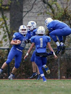 Middlesex's John Kressbach (12) celebrates after scoring a touchdown on Nov. 24, 2016.