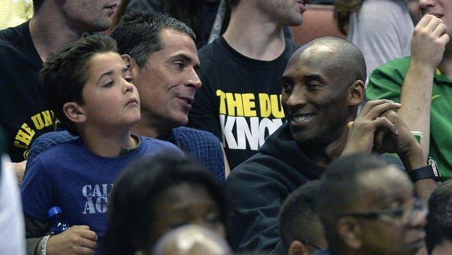 Agent Rob Pelinka sits with Kobe Bryant at a game March 26, 2016, in Anaheim, Calif.