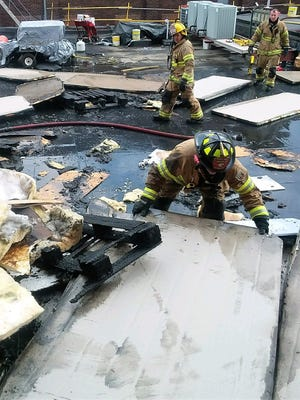 Firefighters sift through charred materials on the roof of the Marion Public Health building, which caught fire and caused a propane tank to explode on Friday.