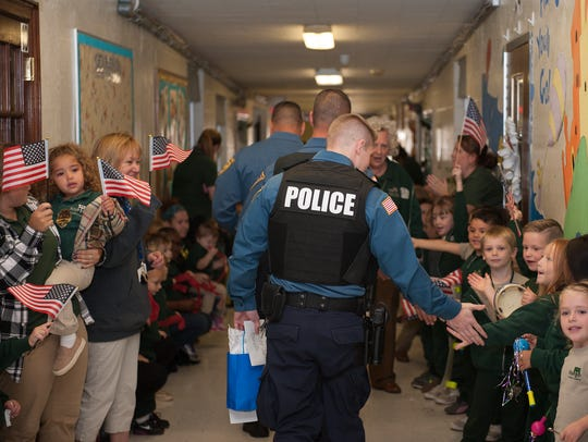 Newfield Police John Borrelli shake hands with students