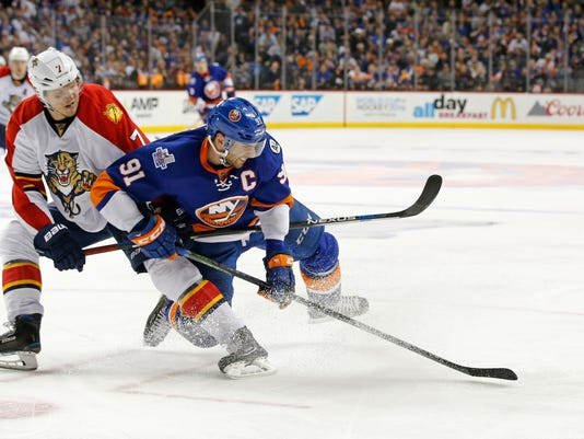 Florida Panthers defenseman Dmitry Kulikov (7) of Russia keeps New York Islanders center John Tavares (91) from the puck in the first overtime period of Game 6 of an NHL hockey first-round Stanley Cup playoff series in New York, Sunday, April 24, 2016. (AP Photo/Kathy Willens)