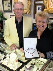 Fred and Terry Rieger pose with custom-made diamond and smoky quartz pendant donated to the Hearts for Hope Special Drawing.