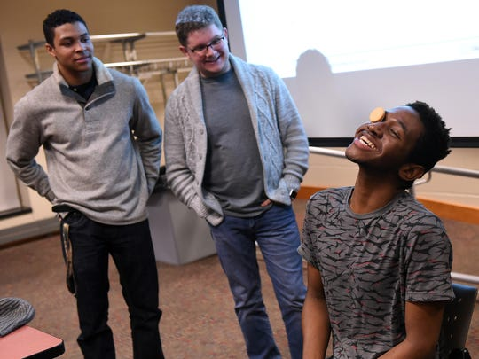 """Wedly Cazr (right) tries to get a cookie from his forehead to his mouth as teammates Roman Lee (left) and Jacob Hutchison (center) look on during a series of """"minute to win it"""" games during International Day at Ohio State University at Newark on Thursday, March 1, 2018."""