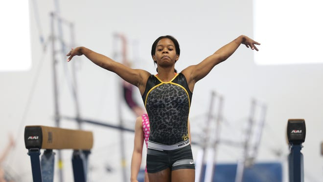 Olympic gold medalist Gabby Douglas participates in warm-ups with other young gymnasts at Chow's Gymnastics on Tuesday, April 29, 2014, in West Des Moines, Iowa.