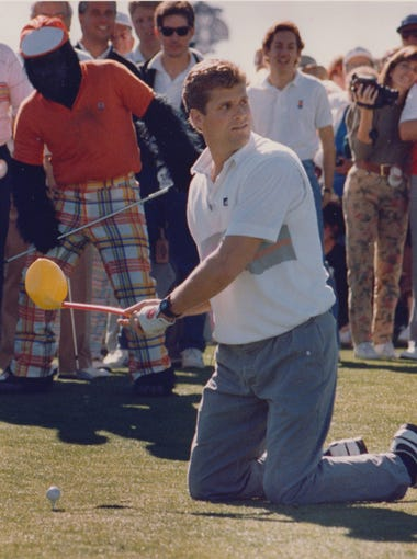 Phoenix Cardinals quarterback, Neil Lomax, gets ready to tee off on the 1st hole with a three-plastic. In the background, the Phoenix Suns gorilla holds Lomax's driver at the Phoenix Open, Jan. 19, 1989.
