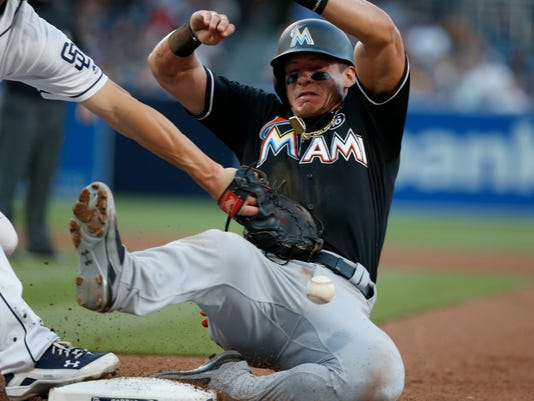 Miami Marlins' Derek Dietrich, right, avoids a pickoff-attempt by San Diego Padres first baseman Wil Myers in the fifth inning of a baseball game in San Diego, Saturday, April 22, 2017. (AP Photo/Christine Cotter)