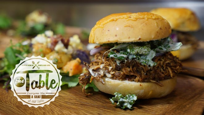 The pulled chicken sandwich is topped  with bacon jam and kale tossed in house-made buttermilk dressing on a cheddar jalapeño bun.