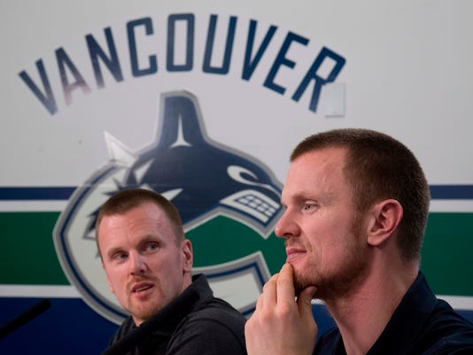 Vancouver Canucks Henrik, right, and Daniel Sedin announce their retirements from hockey during a news conference at Rogers Arena in Vancouver, British Columbia, Monday, April, 2, 2018. (Jonathan Hayward/The Canadian Press via AP)
