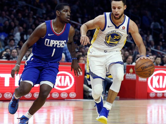 Golden State Warriors guard Stephen Curry, right, dribbles around Los Angeles Clippers guard Jawun Evans during the second half of an NBA basketball game in Los Angeles, Saturday, Jan. 6, 2018. Behind Curry's 45 points, the Warriors won 121-105. (AP Photo/Alex Gallardo)
