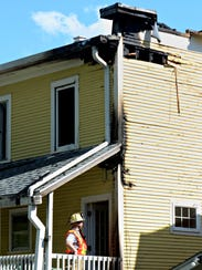 A fire investigator examines damage from a blaze Friday
