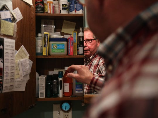 Earl Botkin goes through his medicine in his Evans, W.Va. home.