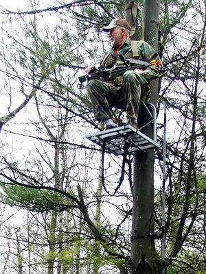 Bowhunter Tim Blank scans the forest from a tree stand in the Town of Erin in this 2006 photo. DEC included tree stand accidents in its hunter safety statistics for the first time in 2017.