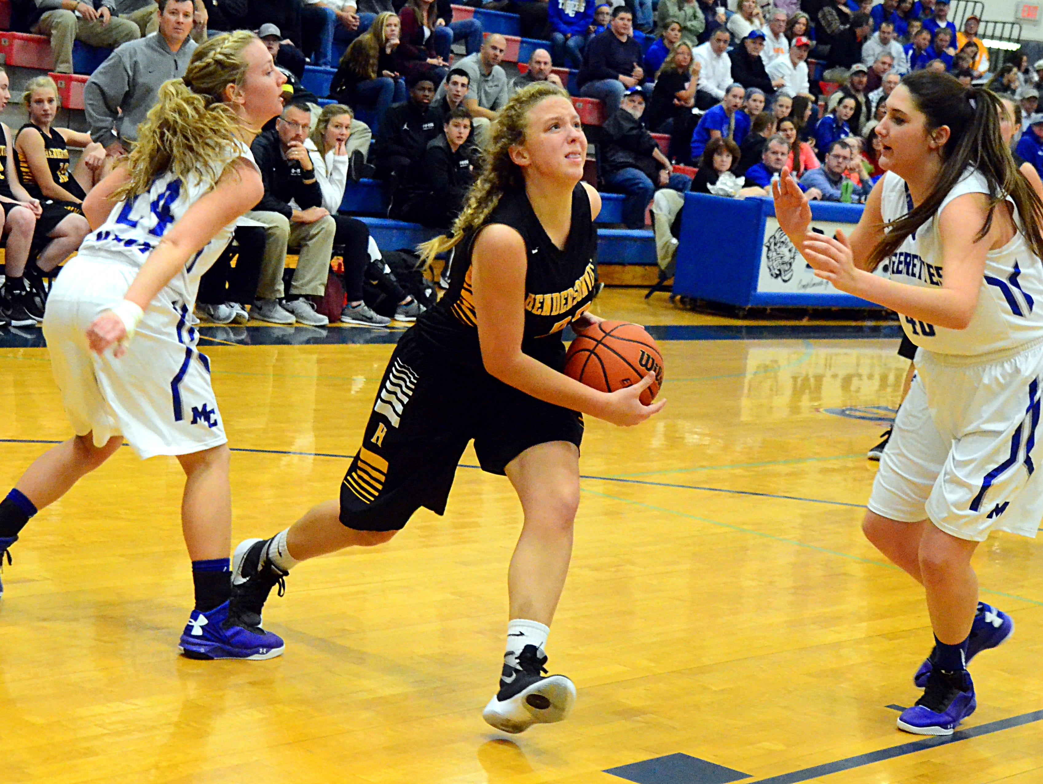 Hendersonville High junior Makensie Cotter drives toward the basket between Macon County juniors Sarah Carter (left) and Kinsley Green during fourth-quarter action.