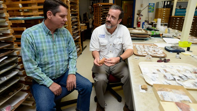 Local historian Tom Garner, left, and John Worth, associate professor of historical archaeology with UWF Department of Anthropology, look at a pottery the rim of a mid-16th century olive jar that was uncovered by Garner in October. The find led to the discovery of the oldest established European multi-year settlement in the United States.