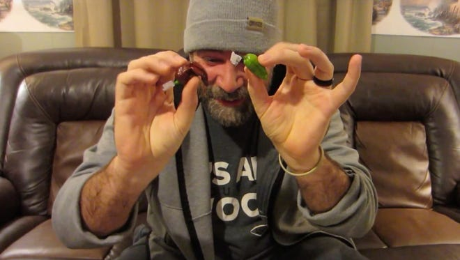 """Martin Nohl, better known as """"Sasquatch,"""" holds up a cholate fatalii pepper, left, and and a seven pot slimer before trying them out in a video recorded on Oct. 31 at his home in Greensburg, Indiana."""