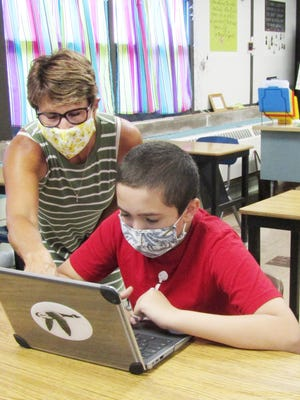 Wethersfield student Jesus Perez works on his assignment last week in Tammy Jackson's seventh grade science class, both following the school's rule of wearing protective face coverings.