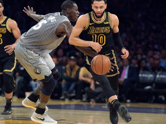 Minnesota Timberwolves center Gorgui Dieng (5) fouls Los Angeles Lakers guard Tyler Ennis (10) during the first half of an NBA basketball game in Los Angeles on Friday, April 6, 2018. (AP Photo/Reed Saxon)
