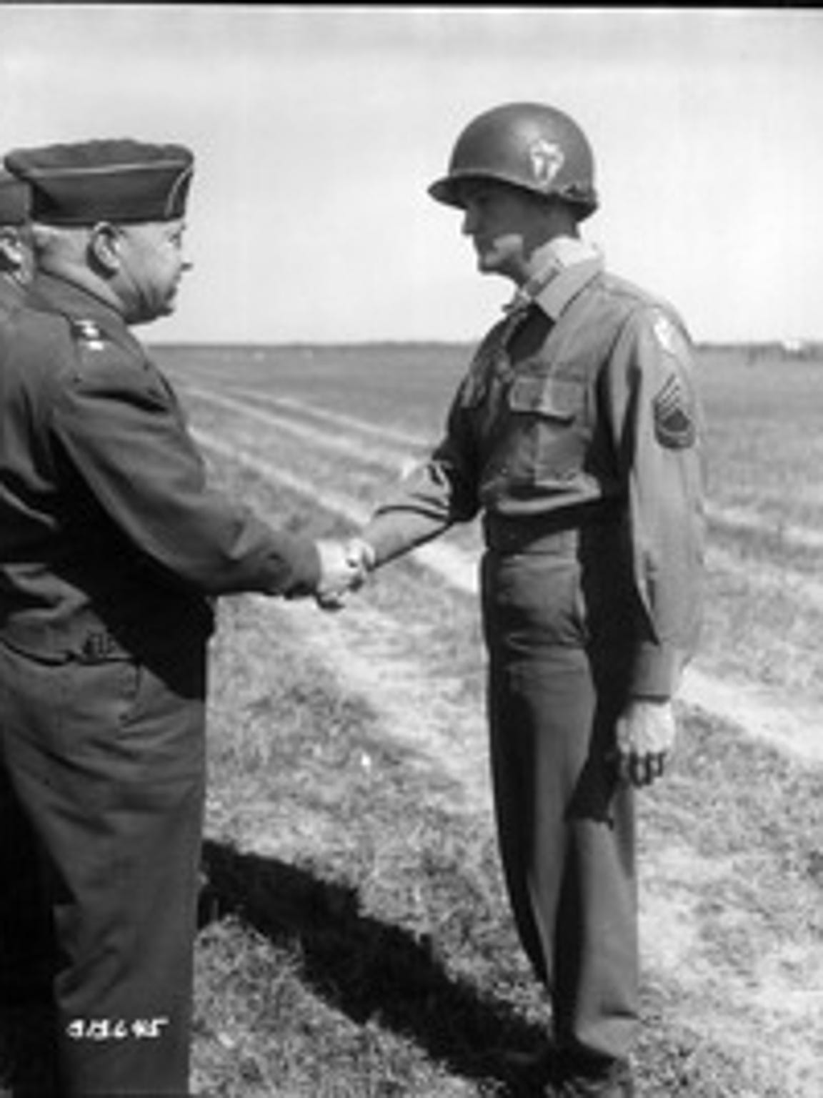 Charles H. Coolidge, right, shakes the hand of Maj.