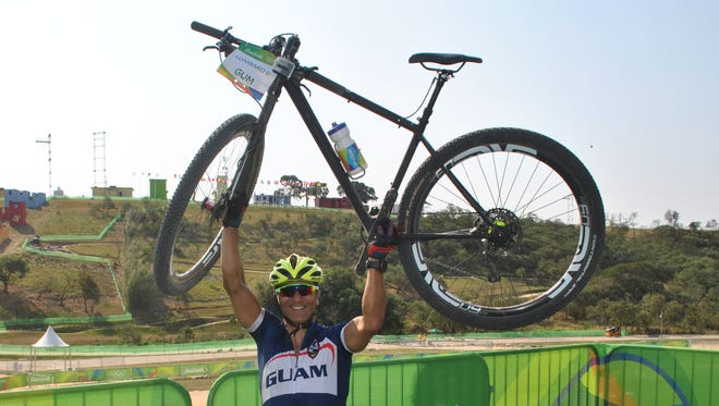 Dr. Peter Lombard near the mountain bike course in Rio de Janeiro, Brazil, with his bike, which can run upward of $8,000.