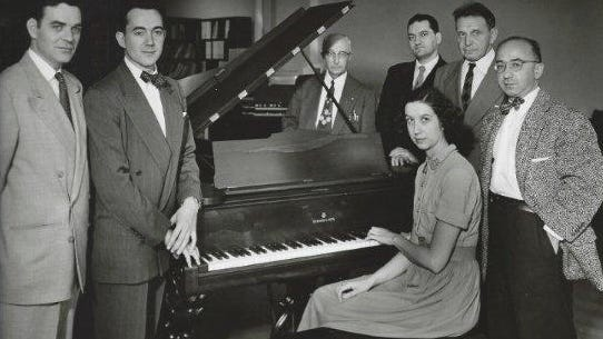 In this photo, believed to be from the 1940s, are, from left, J. Neal Irwin, Edward Edson, William H. Levis, Glance D'Attili, Frank Mittler and Adam Garner. All the men except Irwin and Levis were part of the First Piano Quartet. Seated is Mary T. Light, president of the First Piano Quartet Club, Avon. The group is posed around an 1869 Steinway Grand piano.