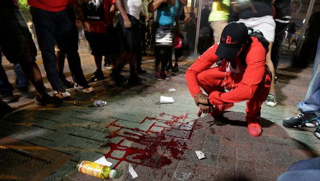 A man squats near a pool of blood after a man was injured during a protest of Tuesday's fatal police shooting of Keith Lamont Scott in Charlotte, N.C.