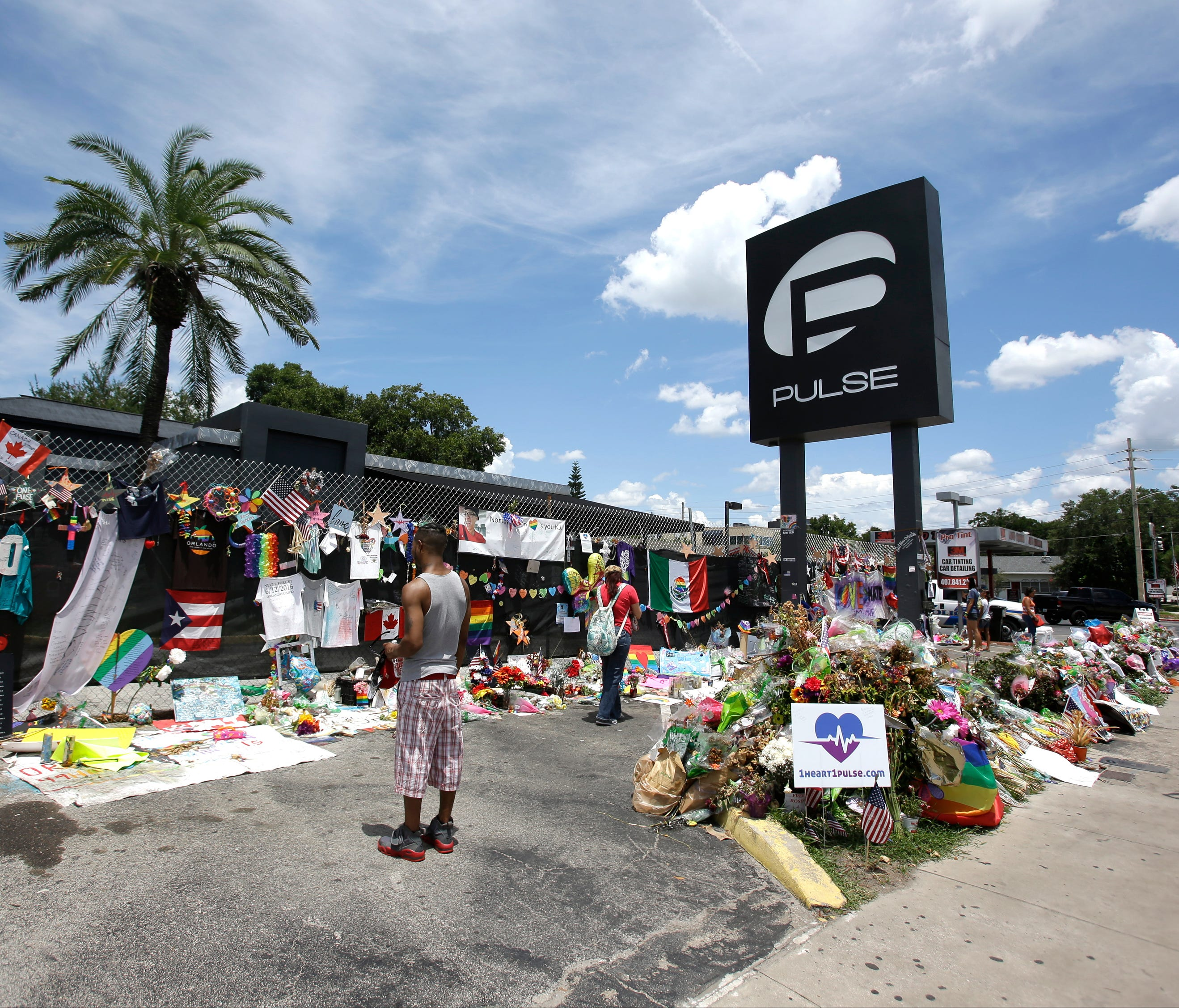 Visitors take photos and leave items at a makeshift memorial outside the Pulse nightclub.